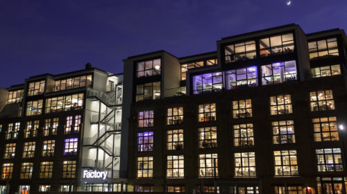 An exterior photograph of Factory Berlin Mitte at night.