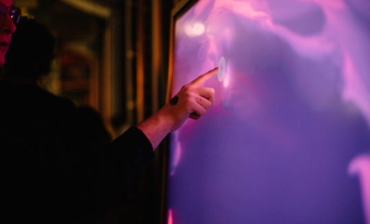A person engages with an interactive art installation at an event.