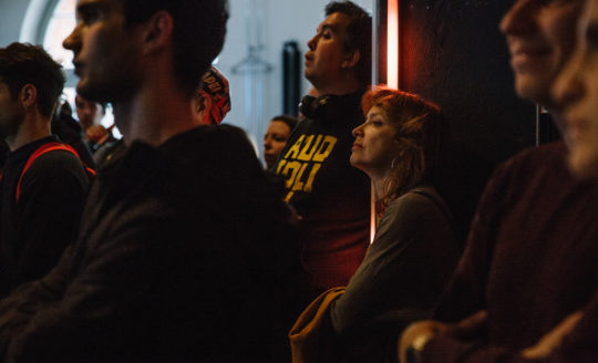 A person at the back of the audience peers to see what's on stage at an event.