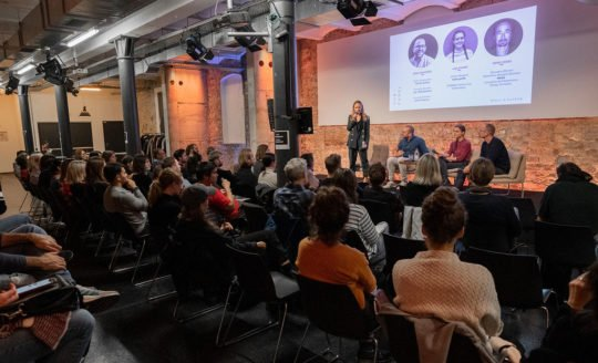 Speakers on a panel, onstage at a Factory Berlin community event